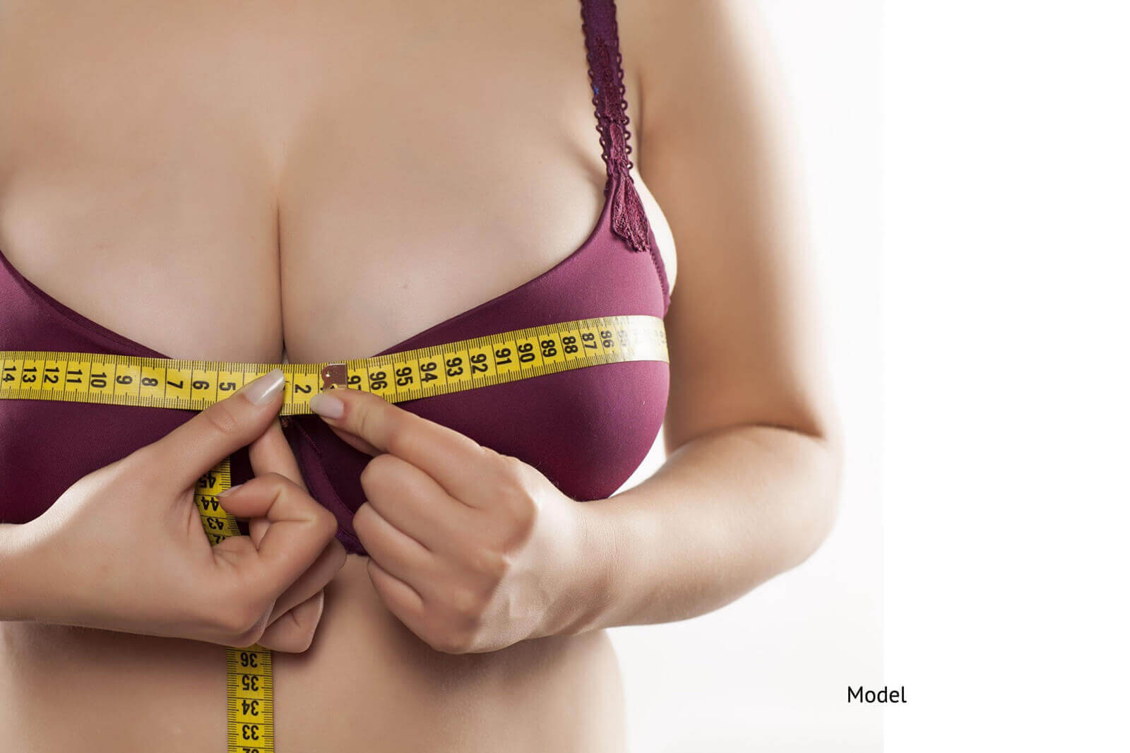 woman measuring her breasts considering breast augmentation