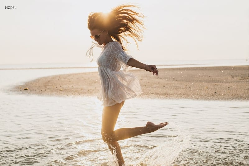 Woman jumping and splashing through the water on beach.